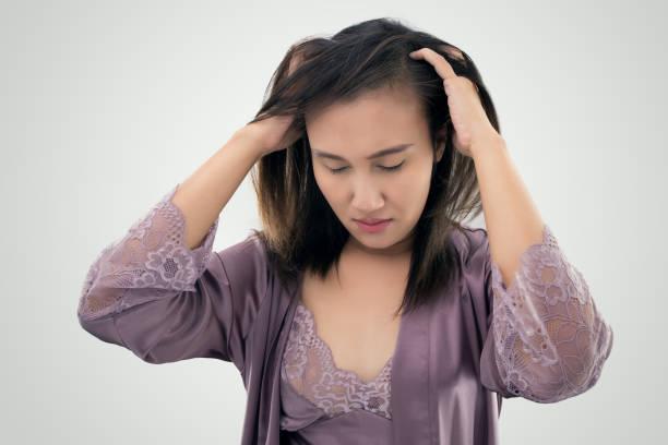 asiatische frauen in juckende kopfhaut vor grauem hintergrund konzept mit schuppen und haarpflege - trockene kopfhaut was tun stock-fotos und bilder