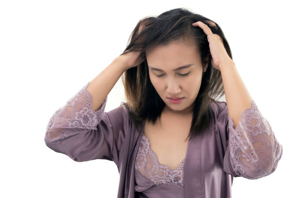 Asian women in itching scalp against gray background Concept with dandruff and hair care stock photo