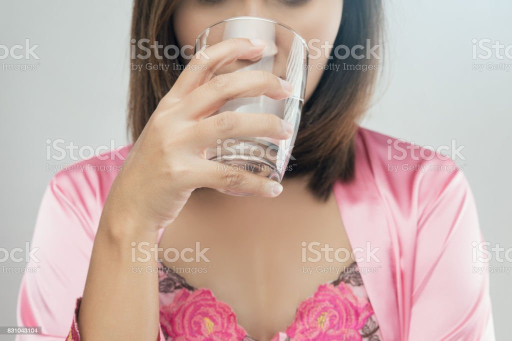 Asian women in  pink satin nightgown drinking water on gray background stock photo