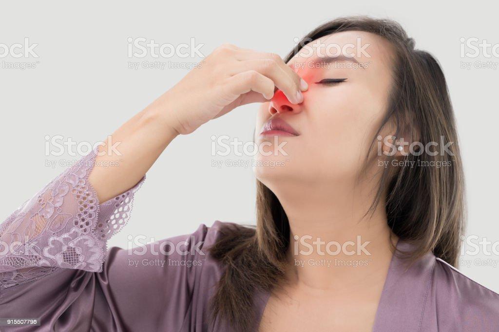 Asiatische Frauen in satin Nachtwäsche mit Nasenbluten vor grauem Hintergrund, die Asiaten schmerzt ihre Nase – Foto