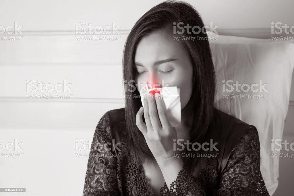 Asiatische Frauen in satin Nachtwäsche mit Nasenbluten oder Nasenbluten vor grauem Hintergrund, Nasenhöhle, die Asiaten ihre Nase schmerzt – Foto