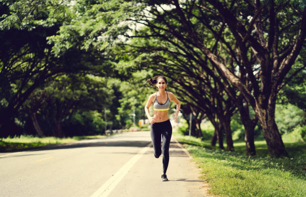 asian women jogging in the morning at the park - carpet runner stock photos and pictures