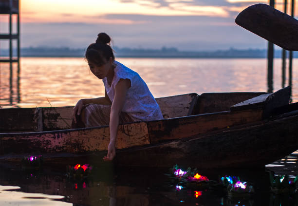 asian women loy kratong festival on the fishing boat in the reservoir, travel thailand. - kratong stock photos and pictures