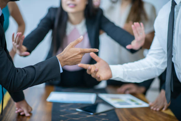 Asian women mediating disagreement A woman in the background is mediating a disagreement between two men in this close-up. A finger is being pointed at one guy while the other is not assuming responsibility. arguing stock pictures, royalty-free photos & images