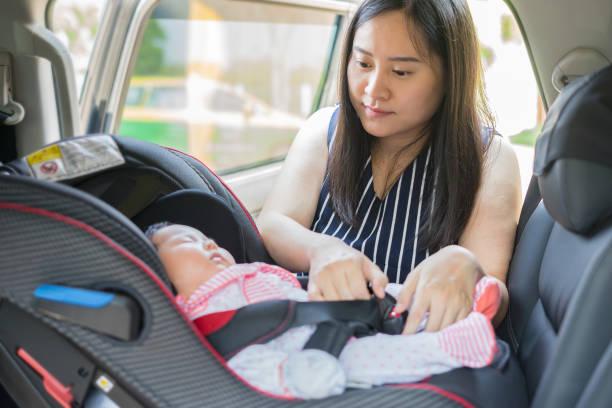 les femmes asiatiques, mère prend soin de sa fille dans une voiture, aide son enfant fixer peu jeune bébé dans le siège auto, ceinture de sécurité pour enfant, parent est garder enfant sécurisé lorsque vous roulez dans un véhicule. - child car sleep photos et images de collection