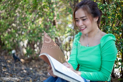 1176252245 istock photo Asian women reading book and smiling and happy Relaxing in a coffee shop after working in a successful office. 1208477448