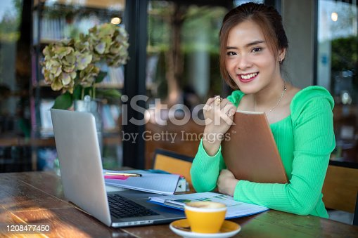 1176252245 istock photo Asian women reading book and smiling and happy Relaxing in a coffee shop after working in a successful office. 1208477450