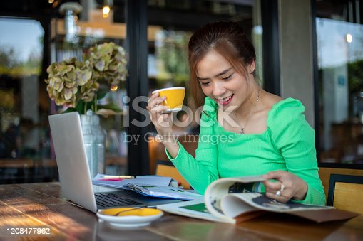 1176252245 istock photo Asian women reading book and smiling and happy Relaxing in a coffee shop after working in a successful office. 1208477962