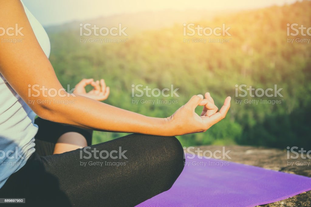 Asian women relax in the holiday. Play if yoga. On the Moutain rock cliff. Nature of mountain forests in Thailand stock photo