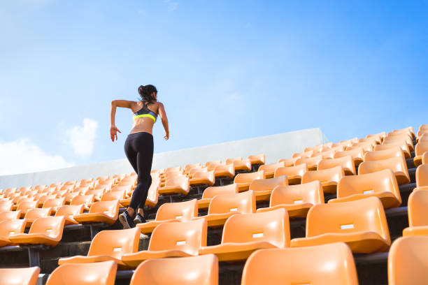 asian women run up the stairs. it is out of strength and cardio. - carpet runner stock photos and pictures