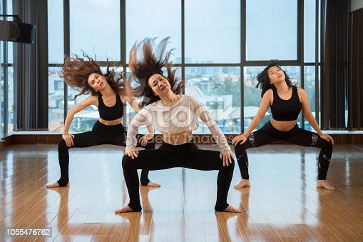 Three attractive Asian ladies shaking hair and looking at camera while dancing in modern studio together