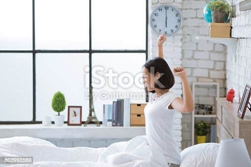 istock Asian women She is in bed and was waking up in the morning. She felt very refreshed. 863993586