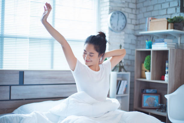 Asian women She is in bed and was waking up in the morning. She felt very refreshed. stock photo