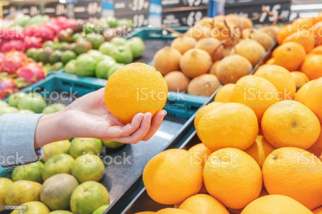 Asian women shopping Orange Fruit and Healthy food vegetables in...