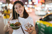 Asian women showing bowl of spicy seafood and coconut ice cream famaus street food in chinatown thailand