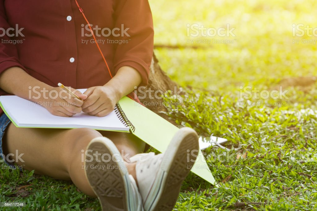 Asian women sitting under the tree with blank notebook foto de stock libre de derechos