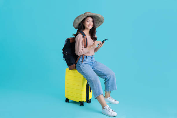 Asian women tourists she is sitting at the airport. She uses a mobile phone. stock photo