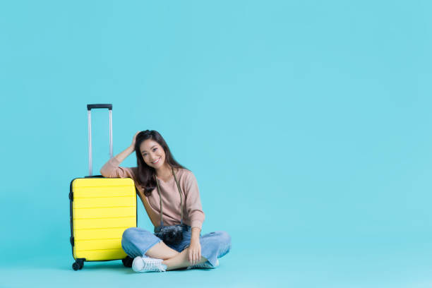 Asian women tourists with a yellow suitcase stock photo