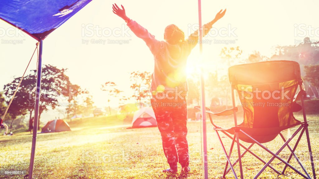 Asian women travel relax in the holiday. camping on the Mountain. light stand in the morning. Thailand stock photo