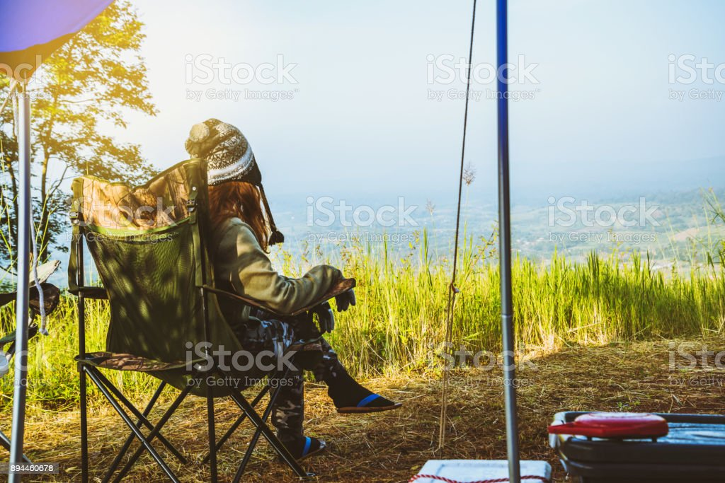 Asian women travel relax in the holiday. camping on the Mountain. sit and rest outdoor chair. Thailand stock photo
