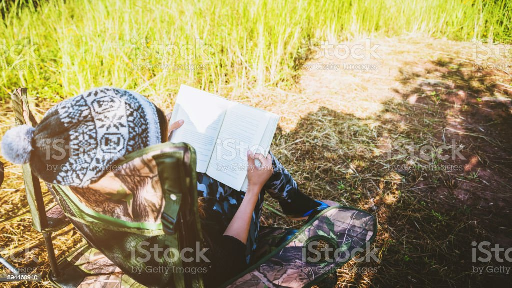 Asian women travel relax in the holiday. camping on the Mountain. sit read a book on the chair. Thailand stock photo