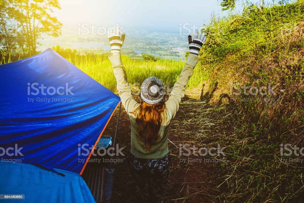 Asian women travel relax in the holiday. camping on the Mountain. Stand up look landscape on the mountain in the morning. Thailand stock photo
