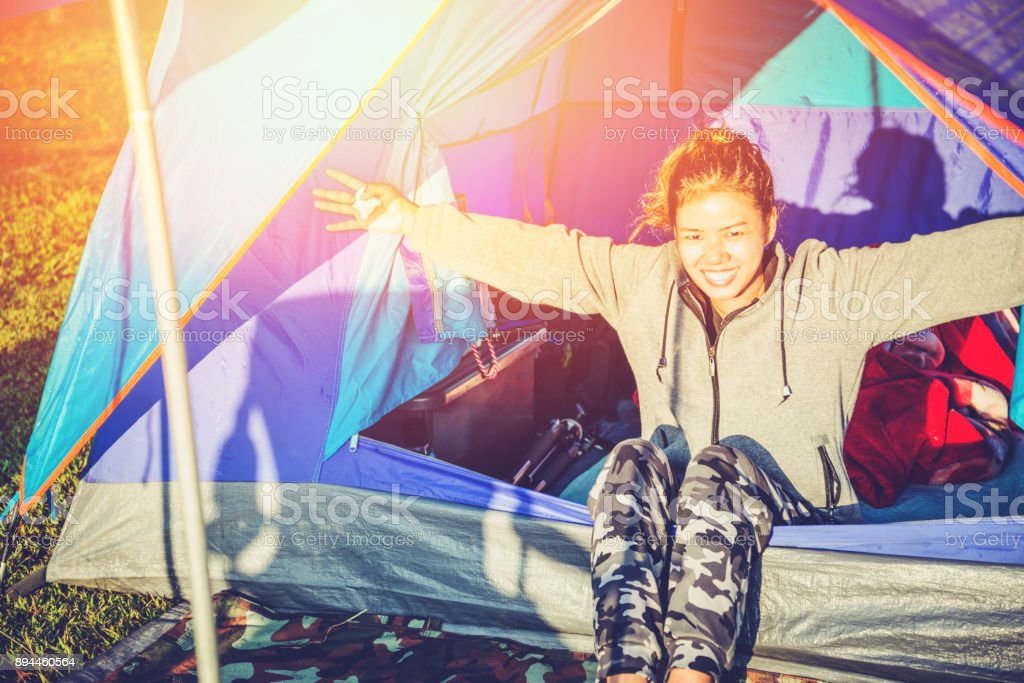 Asian women travel relax in the holiday. camping on the Mountain. wake up sit in a tent. Thailand stock photo