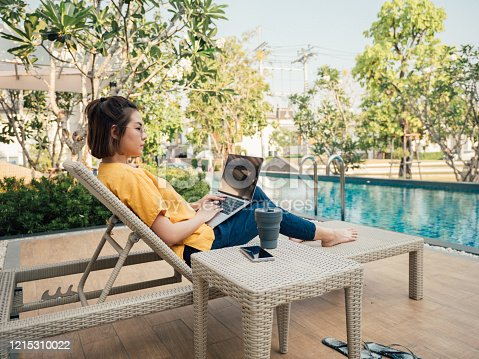 Freelancer working with laptop and smart phone and lying on deck chair near the pool at resort on summer vacation.
