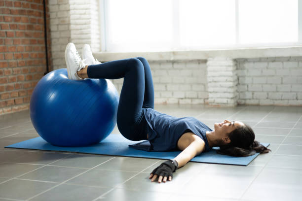 Asian women using an exercise ball in her house. stock photo