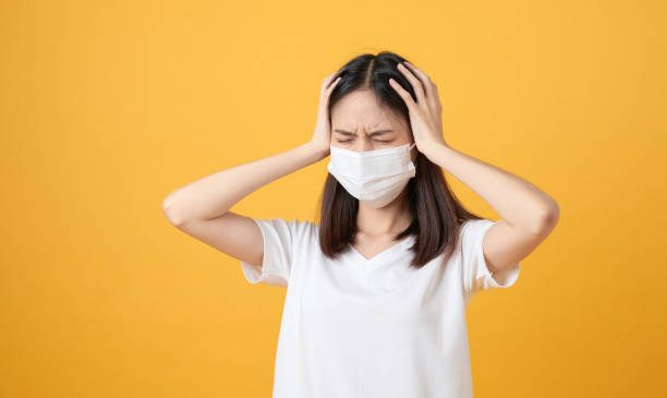 Asian women wear masks to protect disease and the headache from a virus on orange background. stock photo