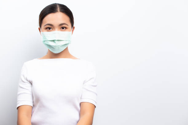 Asian women wear protective masks isolated over white background stock photo