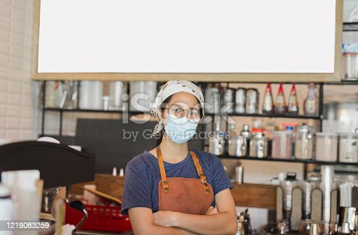 Asian women wearing protective mask standing in cafe during covid-19 preventing