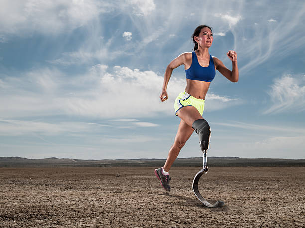 Asian Women With Prosthetic Leg Running In The Desert stock photo