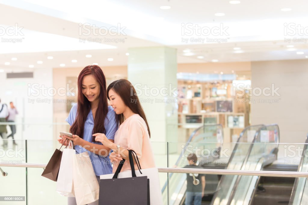 Asian Women with Shopping Bags Looking at Smartphone in Mall stock photo