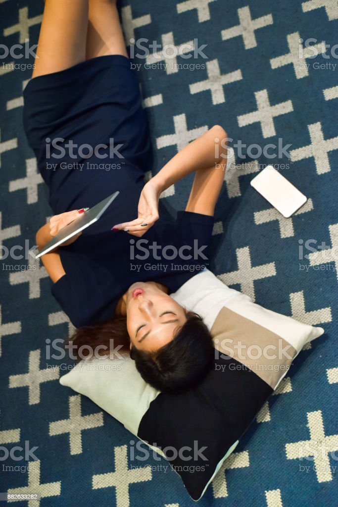 Asian women lays on carpet while using tablet