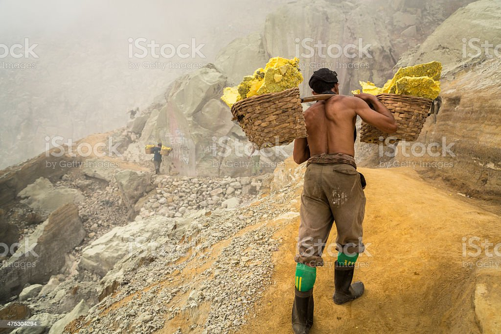 Asian worker carrying baskets of sulfur in Ijen volcano stock photo
