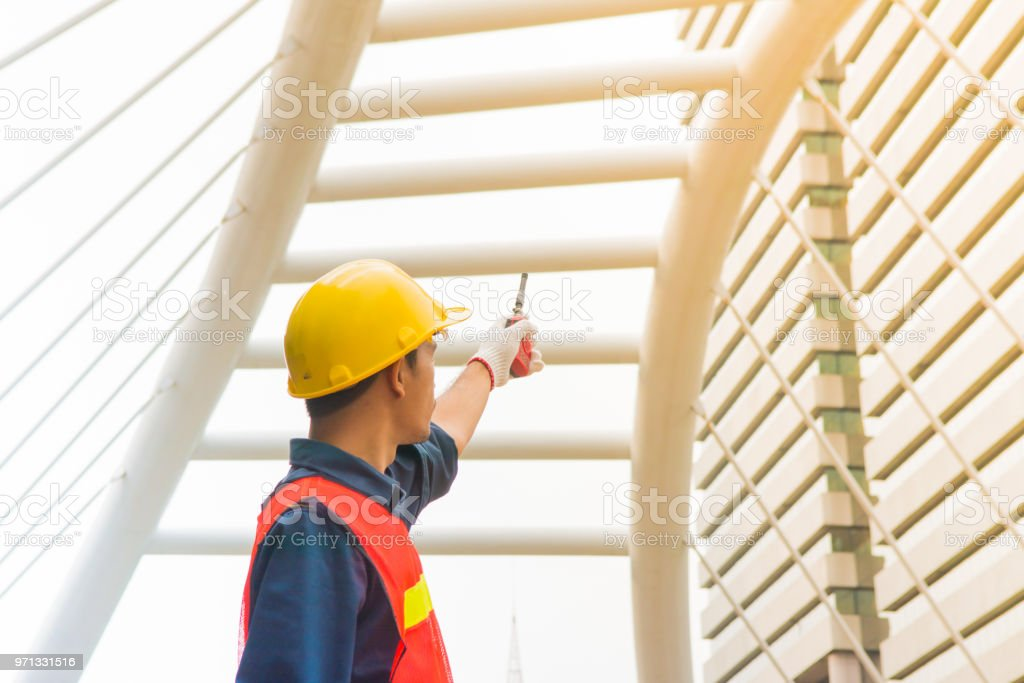 Asian worker is pointing his hand that holding old red walkie talkie during working stock photo