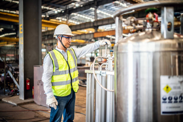 Asian worker operating a gas tank in a factory stock photo