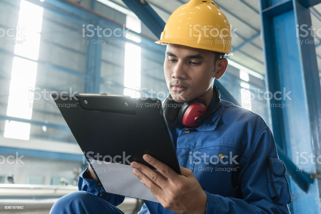 Asian worker writing observations about manufacturing stock photo