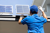 istock Asian workers technicians man installing solar photovoltaic panels for LED lamps on the roof of the house. Exterior solar cell system installation concept 1292357736