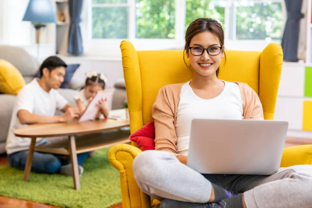 Asian working mom work from home in living room stock photo