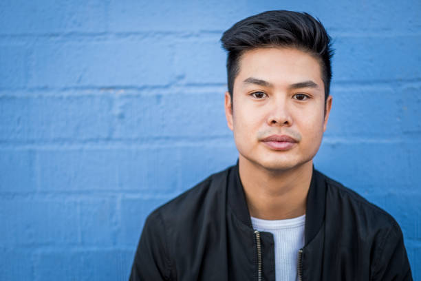 Asian Young Adult Hipster Asian young man standing outdoors against building wall low self esteem stock pictures, royalty-free photos & images