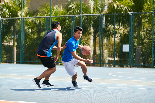 istock asian young adult playing one-on-one basketball 995701724