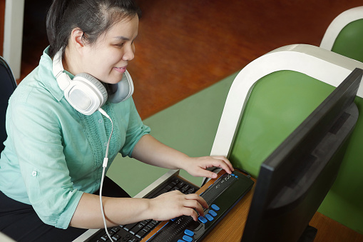 Asian young blind woman with headphone using computer with refreshable braille display or braille terminal a technology device for persons with visual disabilities.