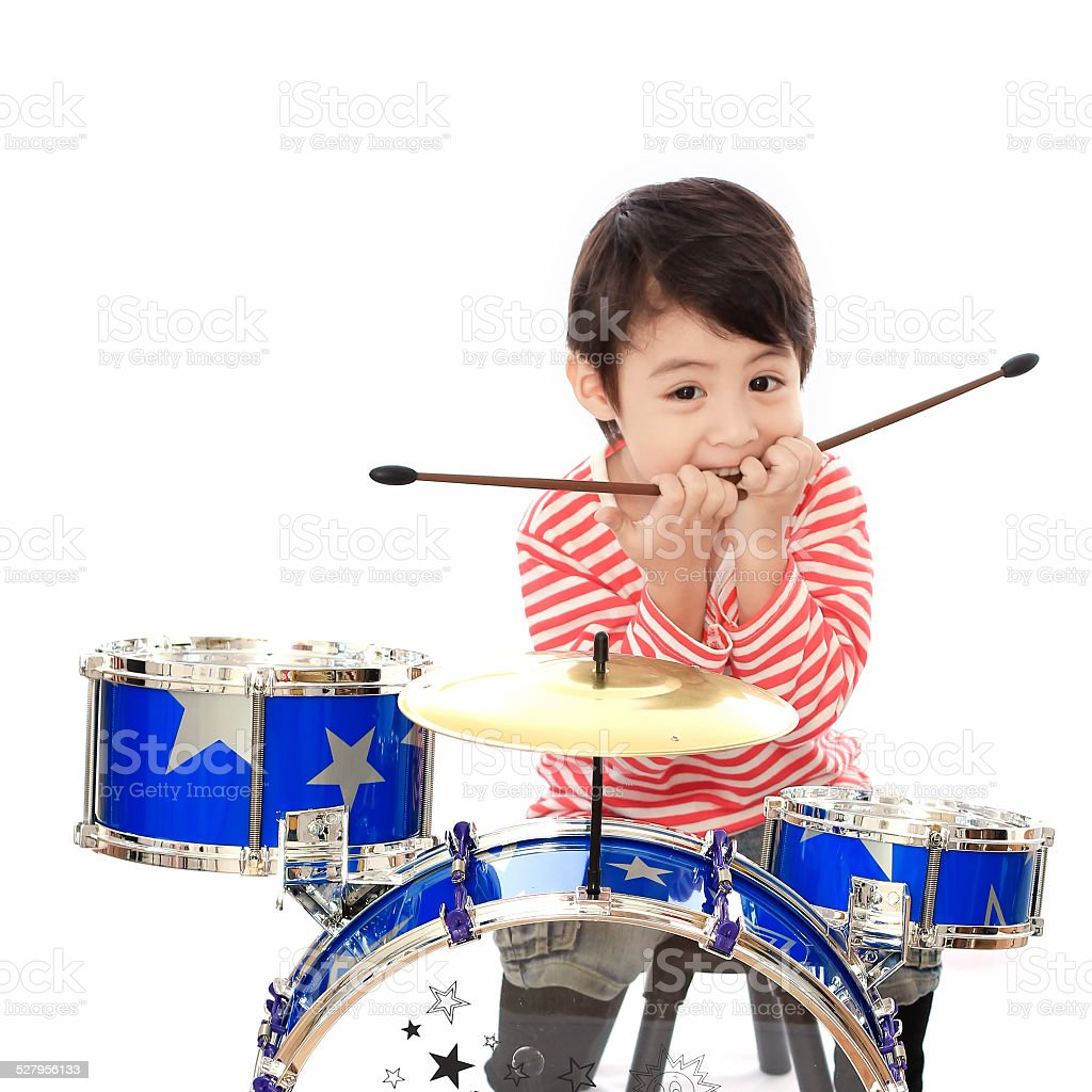 Asian young boy playing drum on white background stock photo