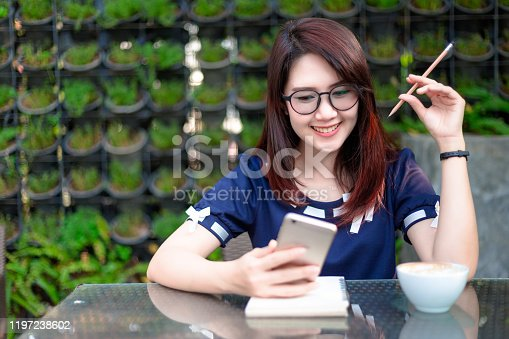 Asian young business woman working on smartphone something making notes in summer park.