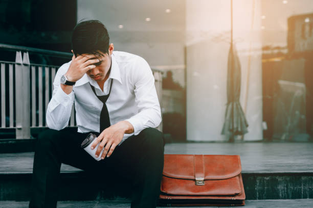 Asian young businessman stress sitting in front office with his hands covering his head against. Asian young businessman stress sitting in front office with his hands covering his head against. mental burnout stock pictures, royalty-free photos & images