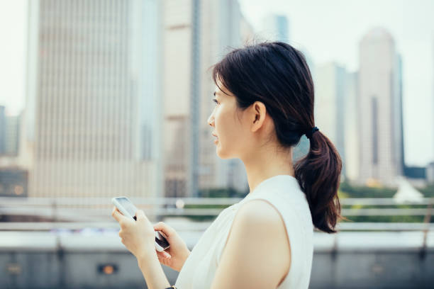 Asian young businesswoman using smartphone outdoors in front of the financial skyscrapers in Lujiazui Financial District, Shanghai,China stock photo