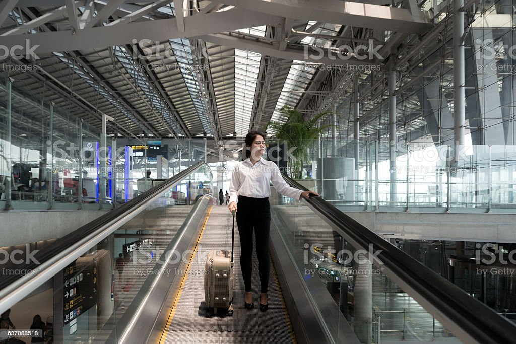 Asian young businesswoman with luggage down the escalator in airport stock photo