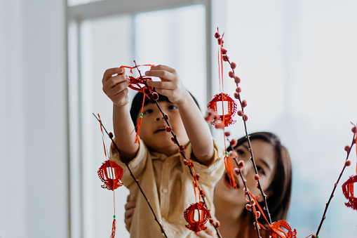 Image of an Asian young chinese boy helping mother to hang Chinese New Year decoration on a plant
